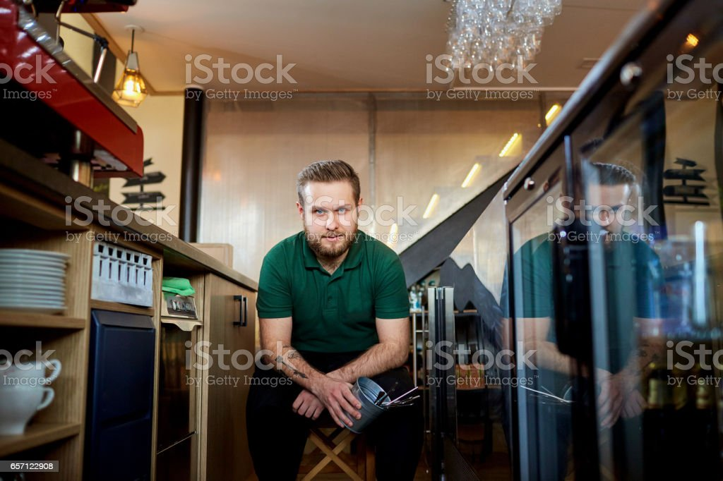 Bartender barista in a break at  workplace in the bar stock photo