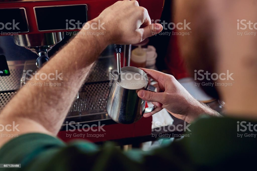 Bartender, barista makes hot milk in a coffee machine behind the stock photo