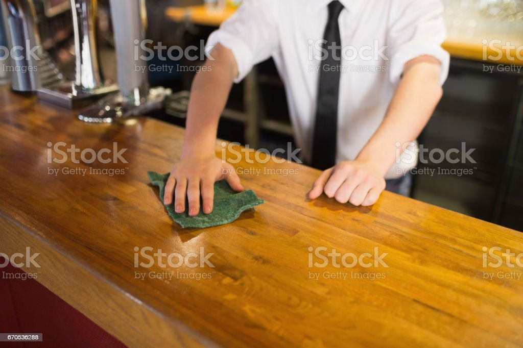 Bartender cleaning bar counter stock photo