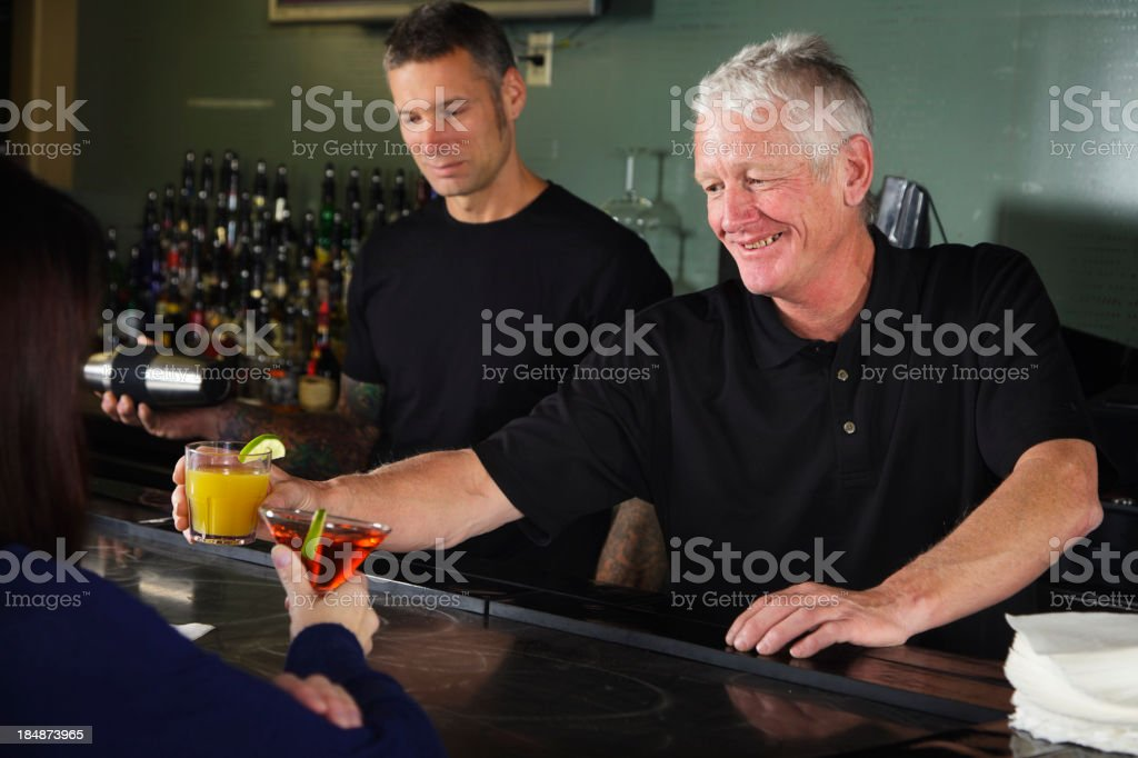 Bartender Handing a Drink royalty-free stock photo