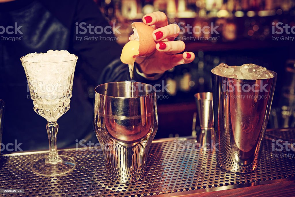 Bartender is adding egg to the glass, toned stock photo