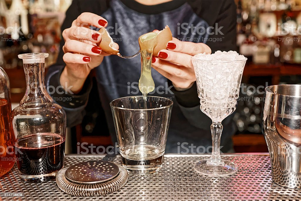 Bartender is adding egg white to the glass, toned stock photo