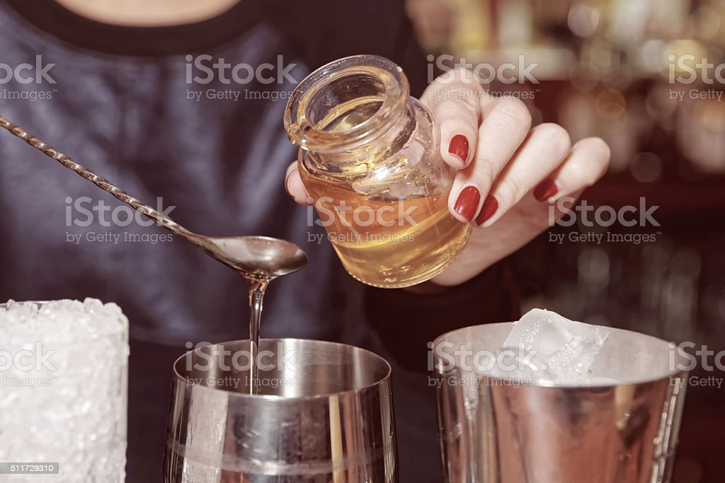 Bartender is adding honey to the glass, toned stock photo