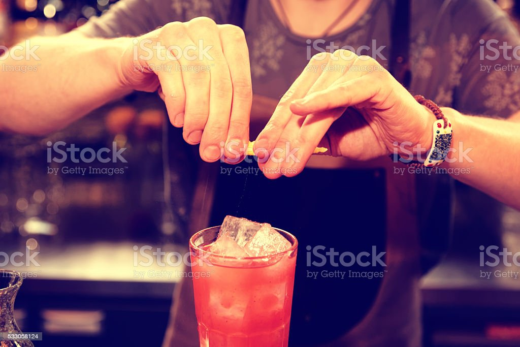 Bartender is adding zest to the cocktail, toned stock photo