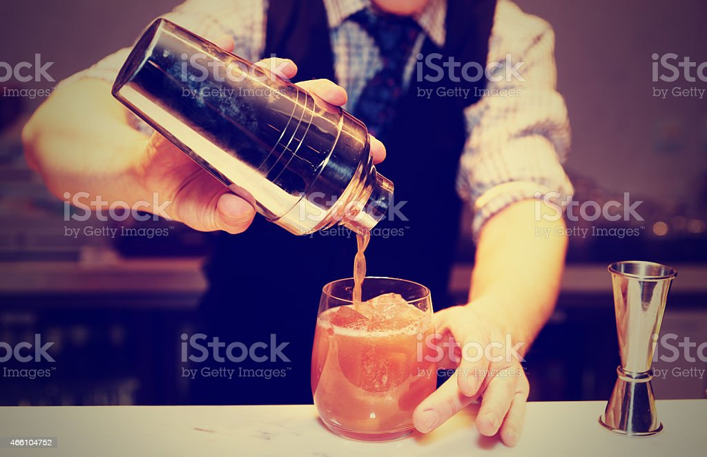 Bartender is making a cocktail, toned stock photo
