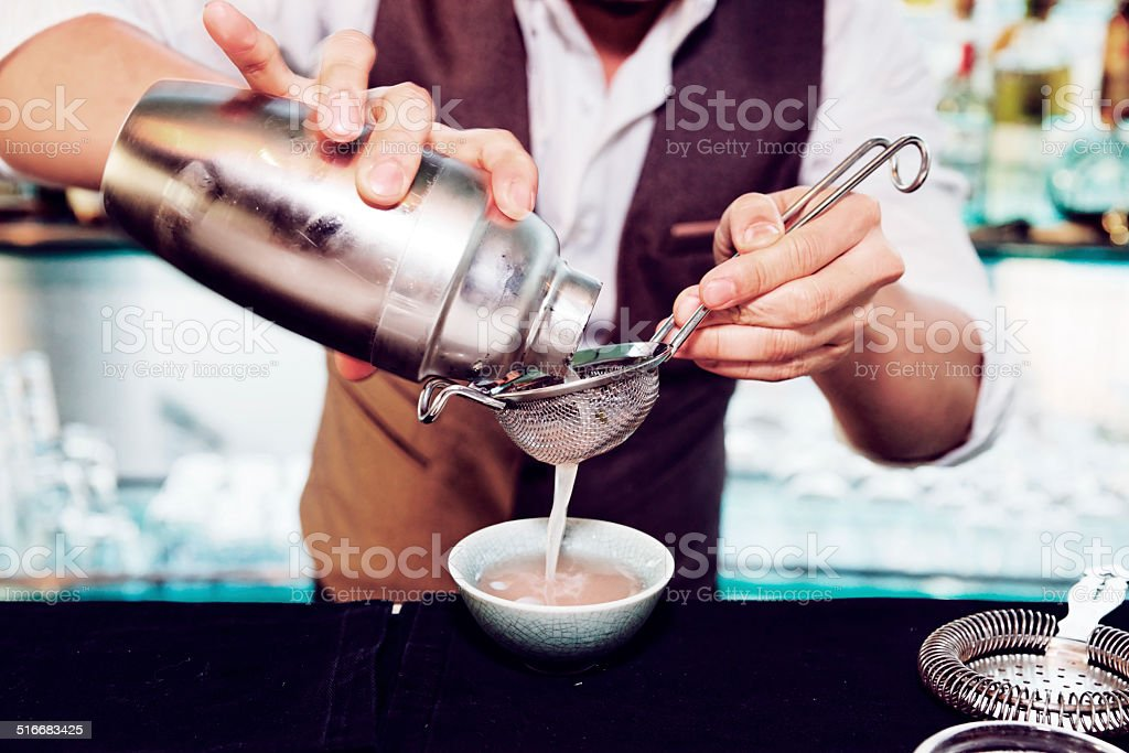 Bartender is making cocktail, toned stock photo