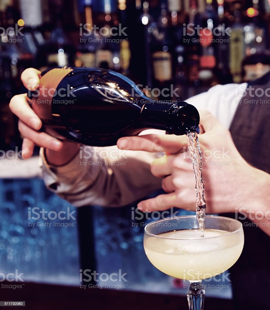 Bartender is pouring sparkling wine, toned stock photo
