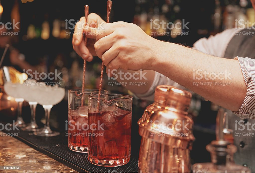 Bartender is stirring cocktails, toned image stock photo