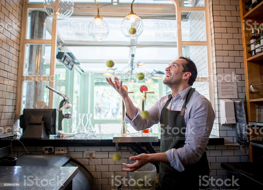 Bartender juggling with lemons at the bar stock photo