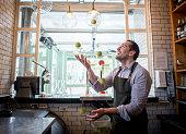 Bartender juggling with lemons at the bar