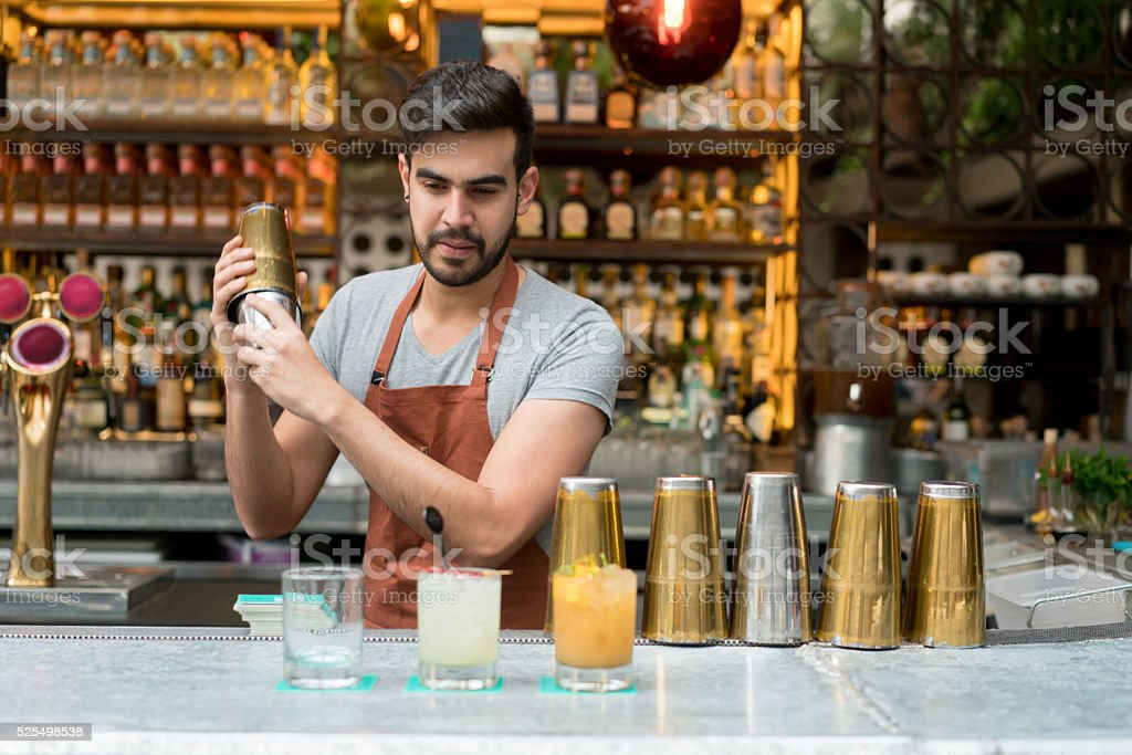Bartender making cocktails at a bar stock photo