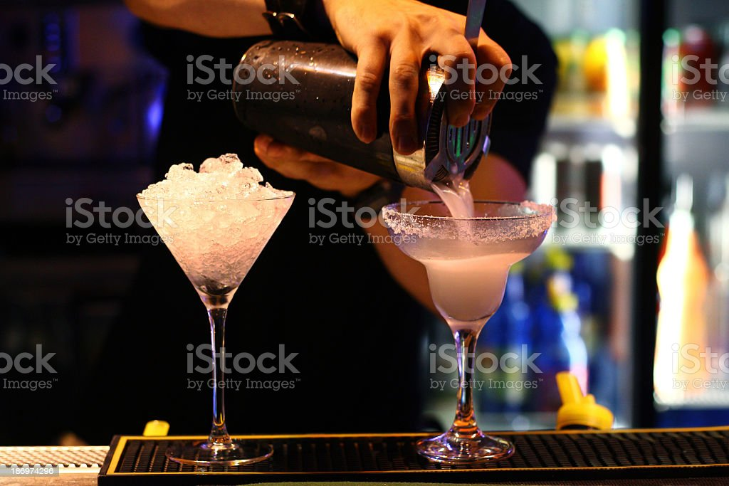 A bartender making cocktails in martini glasses stock photo