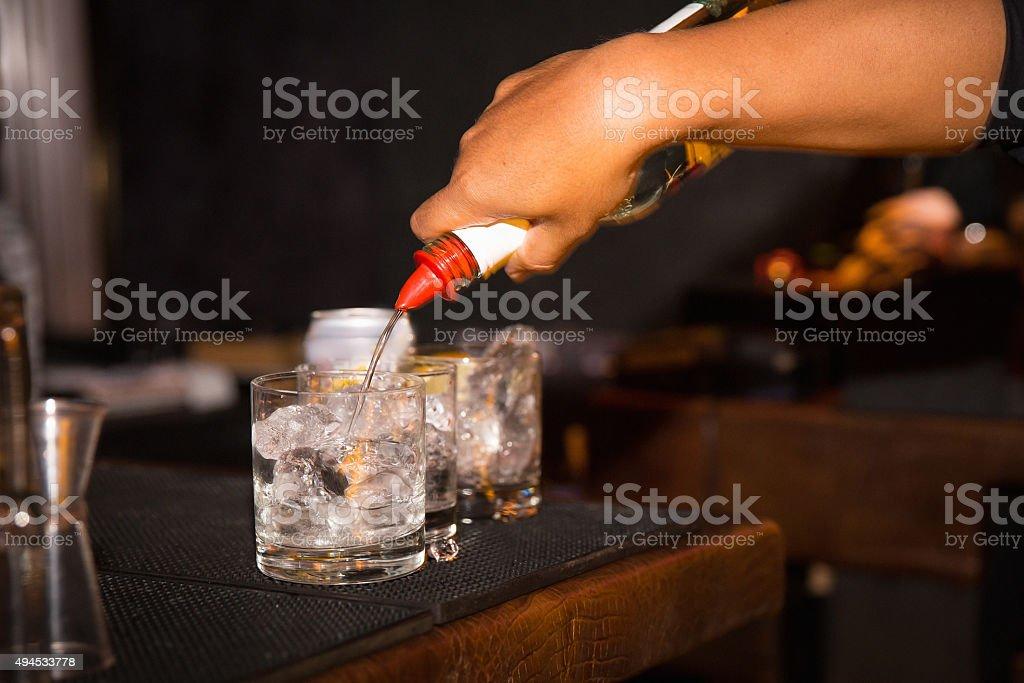 Bartender man pouring alcohol bottle stock photo