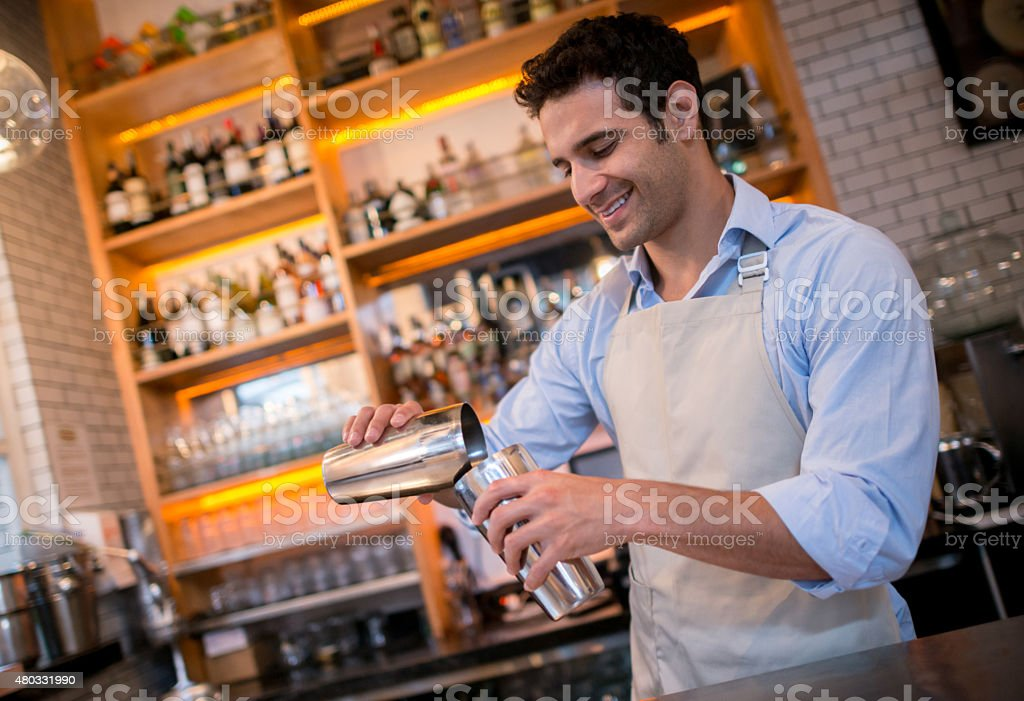 Bartender mixing drinks at a bar stock photo