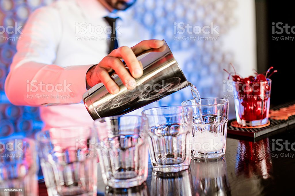 Bartender mixing drinks stock photo