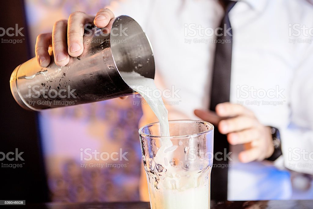 Bartender pouring a cocktail from the cocktail shaker stock photo