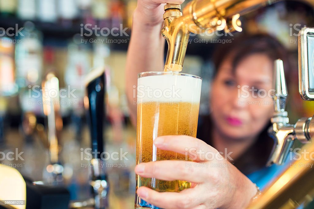 Bartender pouring a pint of beer stock photo