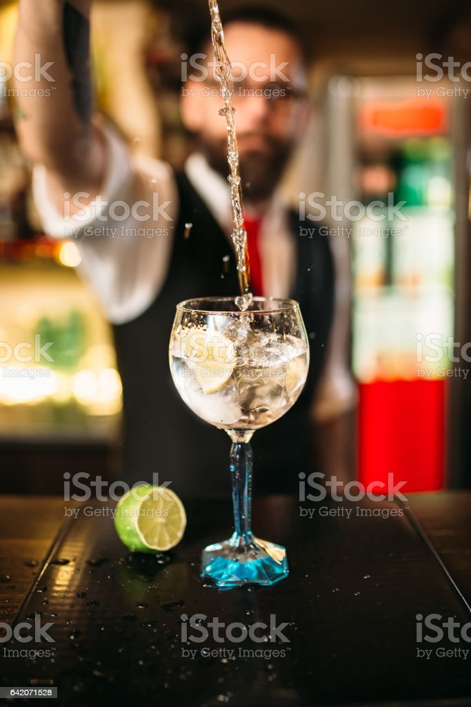 Bartender pouring alcoholic drink in glass stock photo