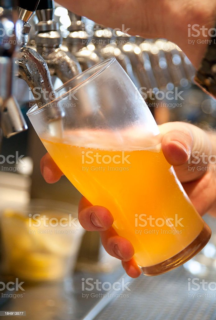 Bartender pouring beer into a glass from the tap royalty-free stock photo
