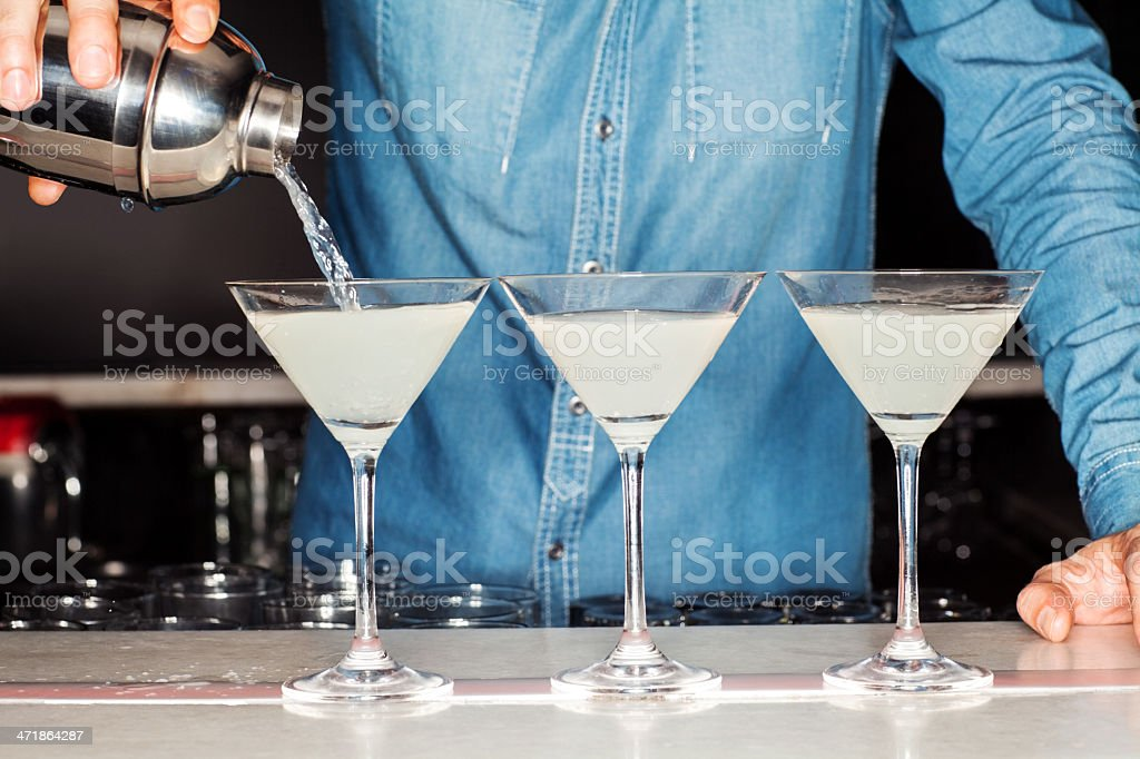 Bartender Pouring Cocktail Into Martini Glasses At Counter stock photo
