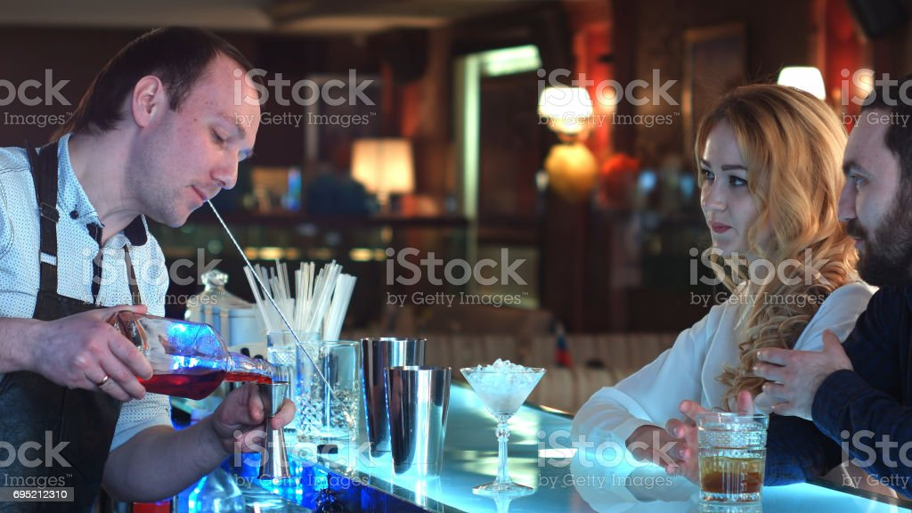 Bartender pouring mixed cocktail for clients in a bar stock photo