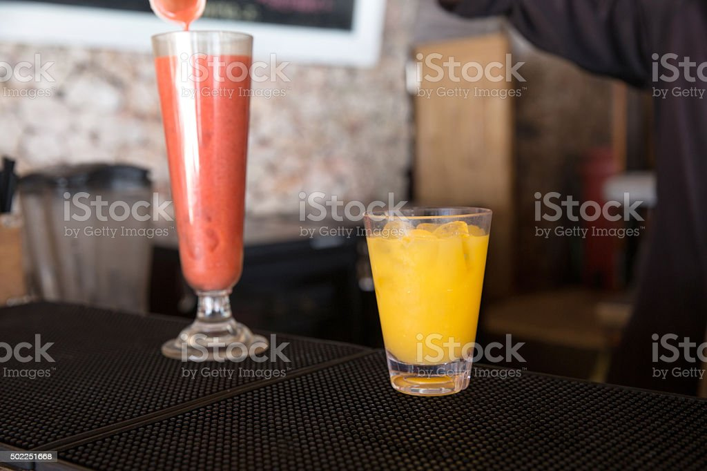 Bartender pouring strawberry smoothie stock photo