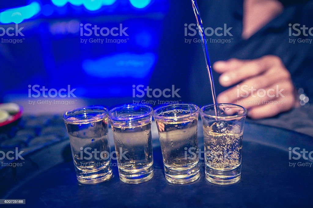 Bartender pouring tequilla on the bar stock photo