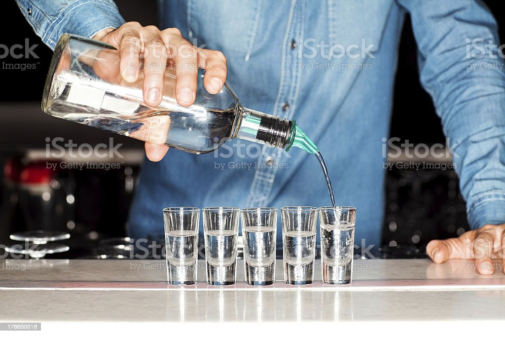 Bartender Pouring Vodka Into Shot Glasses At Bar Counter stock photo