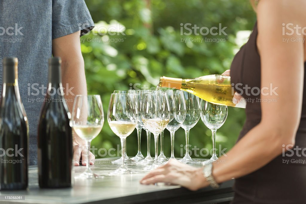 Bartender Pouring White Wine from Bottle for Outdoor Winery Tasting stock photo
