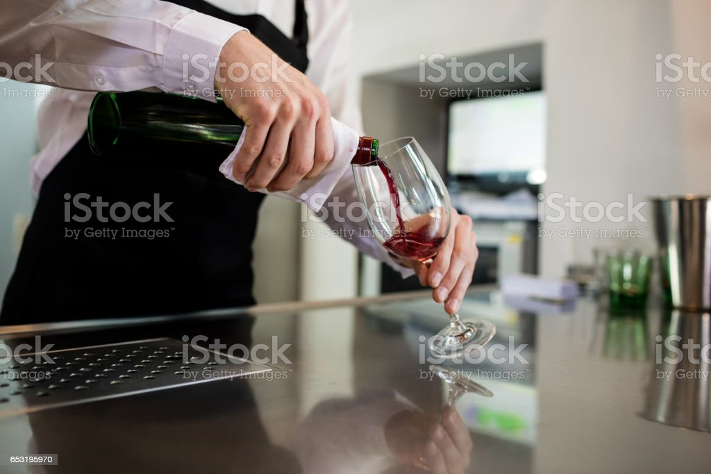 Bartender pouring wine in glass at bar counter stock photo