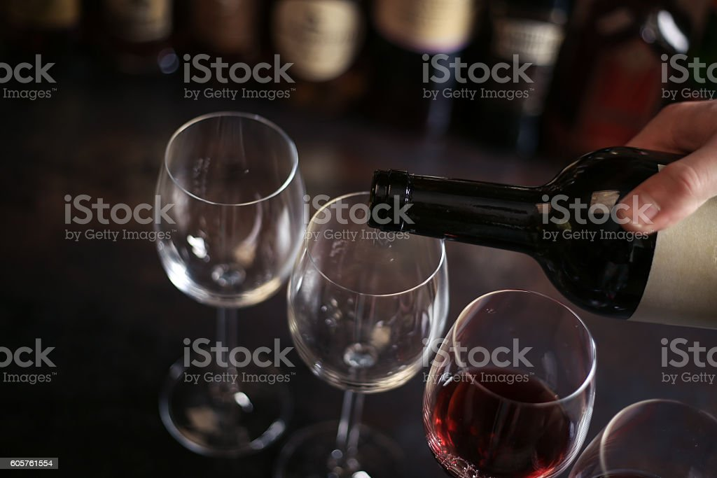 bartender pours a glass of red wine stock photo