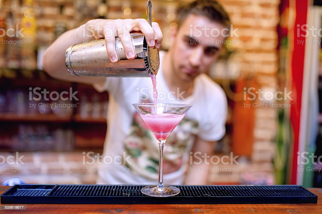 bartender preparing and pouring cosmopolitan alcoholic cocktail stock photo