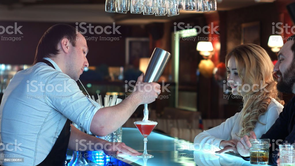 Bartender preparing cocktail for a girl who is looking forward to sitting at the bar stock photo