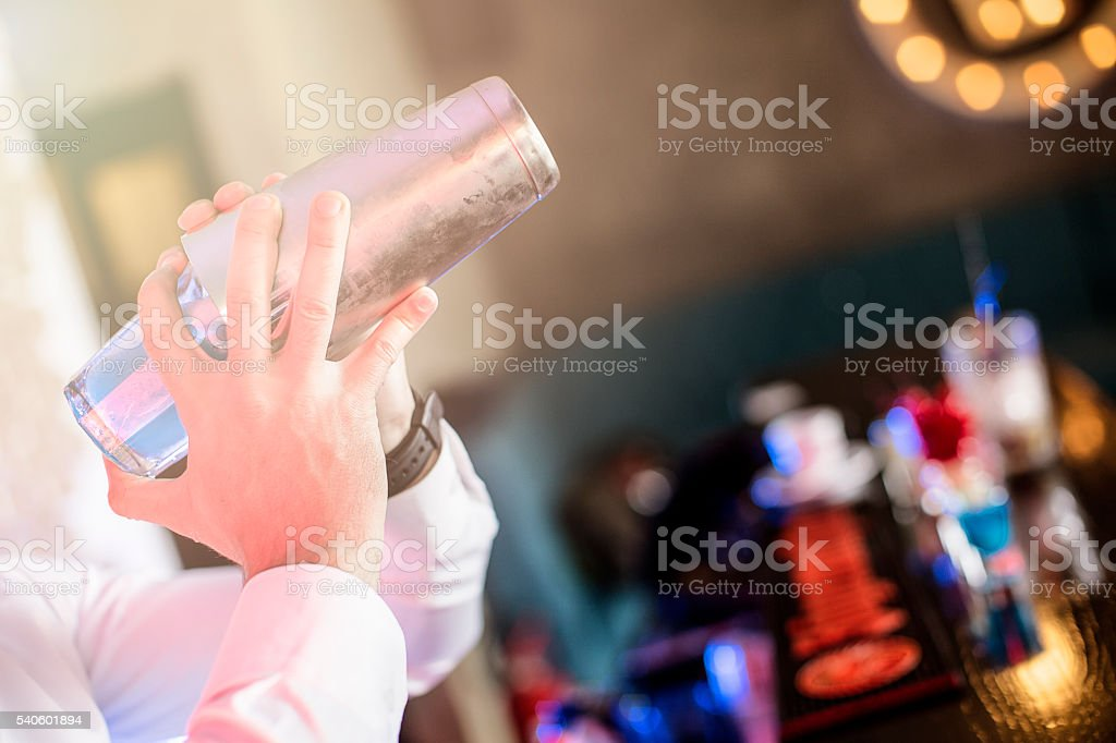 Bartender preparing cocktail in the shaker stock photo