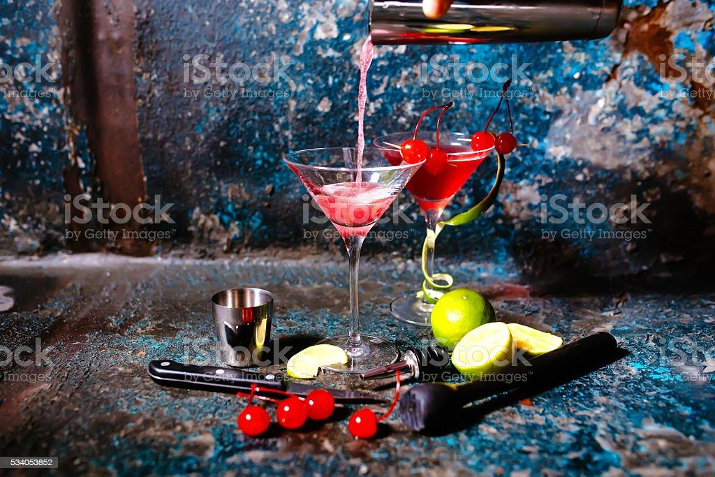 bartender preparing cranberry juice and vodka - cosmopolitan alcoholic cocktail stock photo