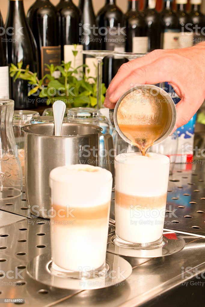 Bartender preparing Latte Macchiato stock photo