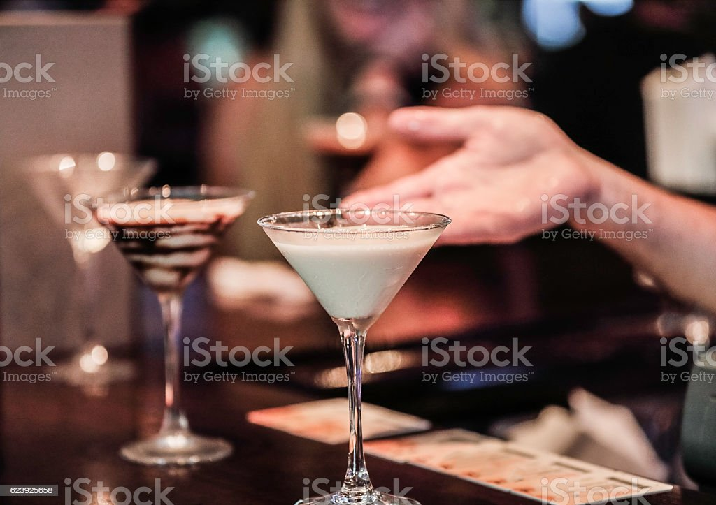 Bartender presenting  Martini Glasses filled with speciality liquor drinks stock photo