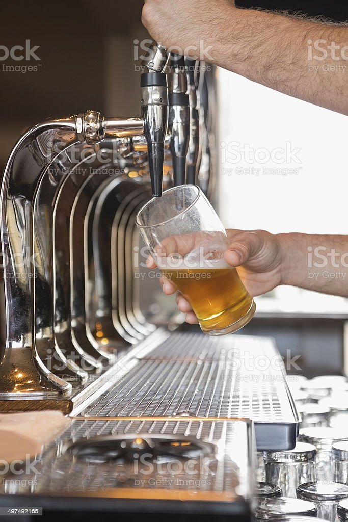 Bartender pulling a pint of beer stock photo