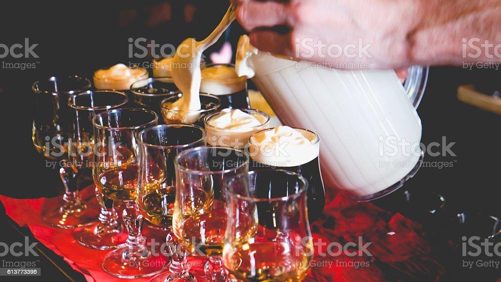 Bartender putting cream on top Irish coffee stock photo