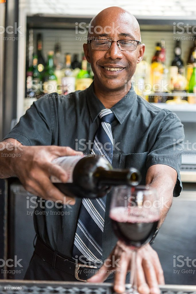 Bartender serving a glass of red wine stock photo