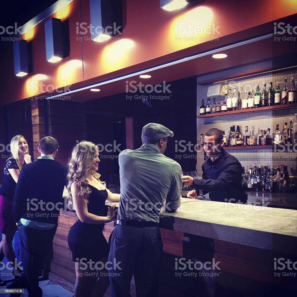 Bartender serving couple at bar stock photo
