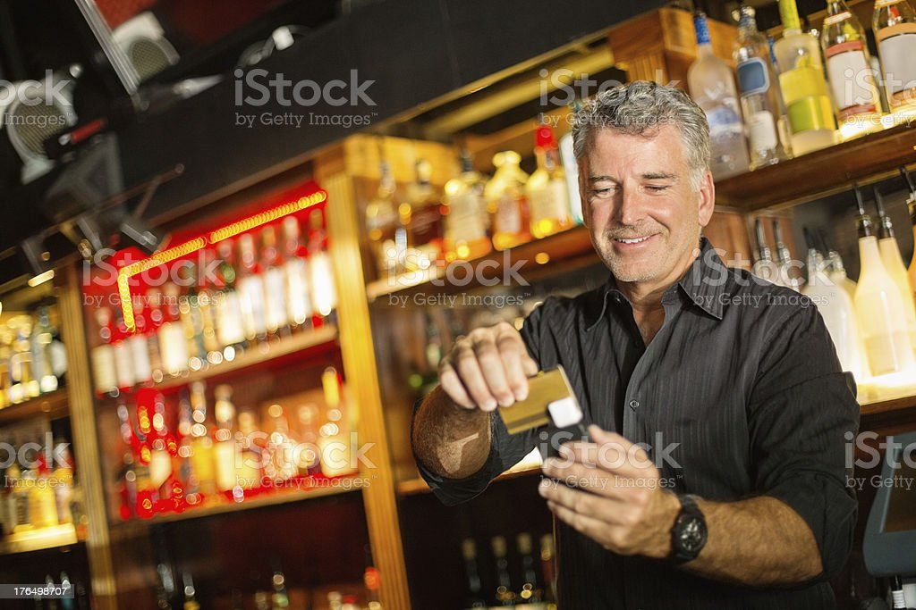 Bartender Swiping Credit Card Using Reader Attached To Mobile Ph stock photo