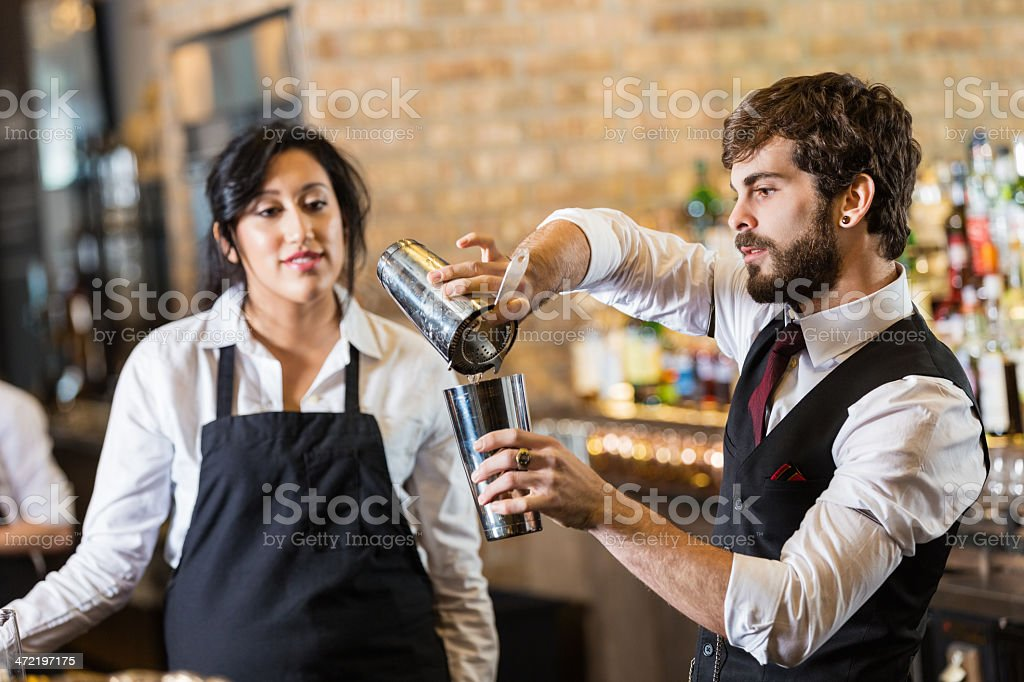 Bartender teaching new trainee to make mixed drink in bar stock photo