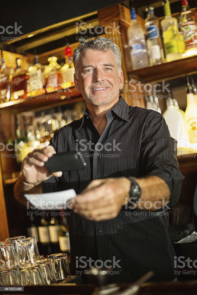 Bartender Using Smart Phone To Deposit Check In Bar stock photo
