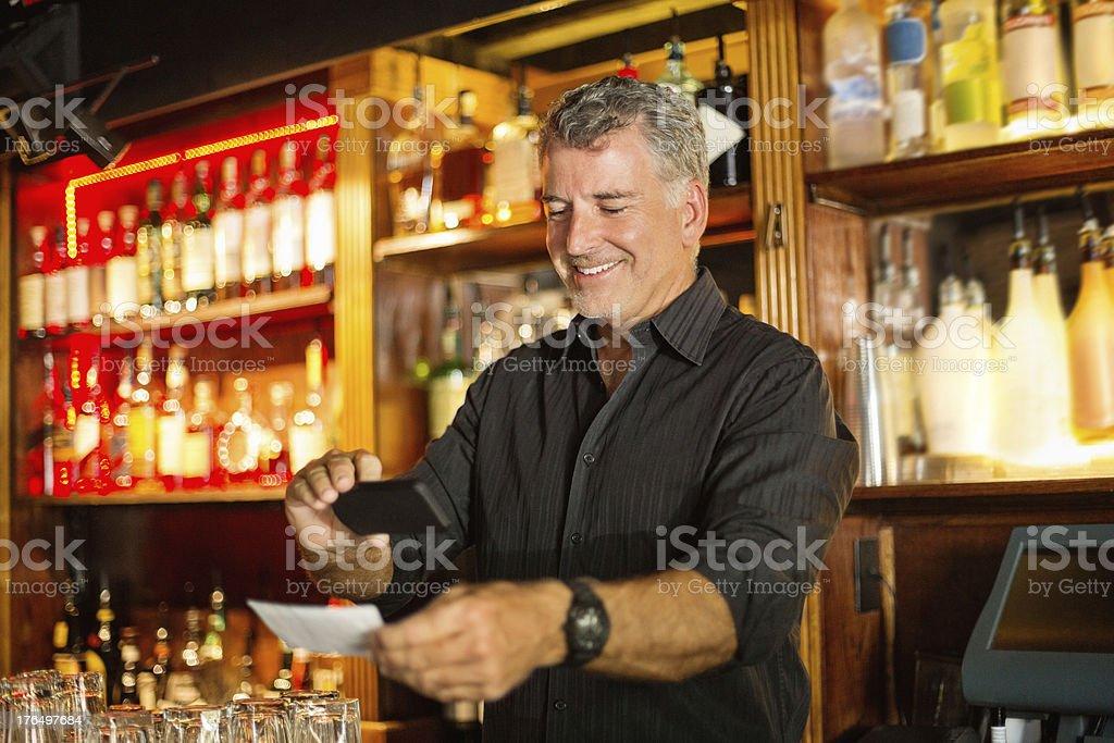 Bartender Using Smart Phone To Deposit Check stock photo
