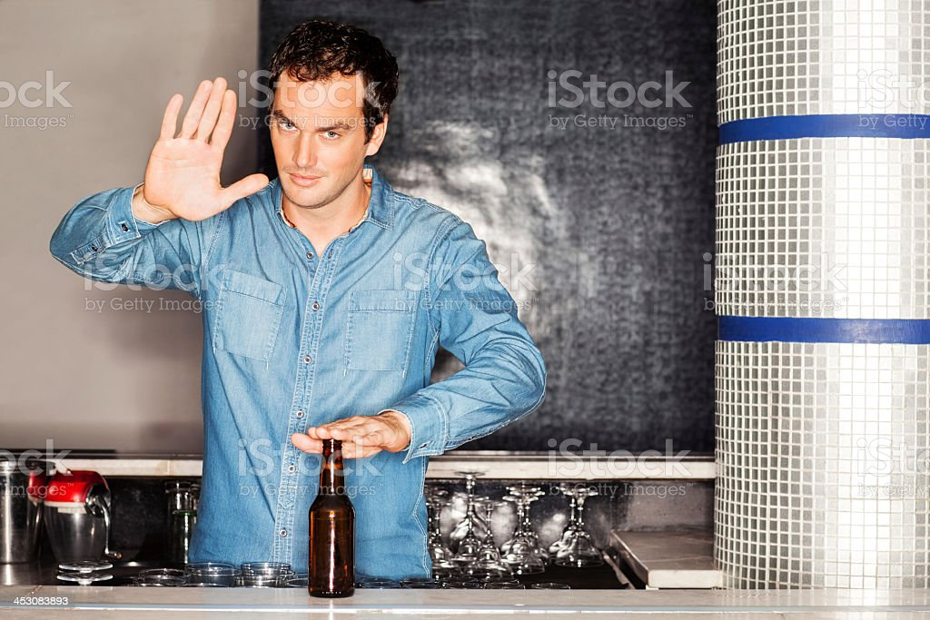 Bartender With Beer Bottle Gesturing Stop Sign At Counter royalty-free stock photo