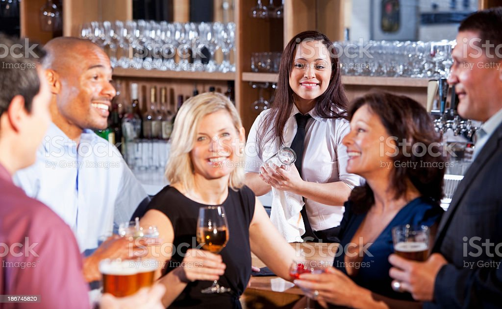 Bartender with group at bar stock photo