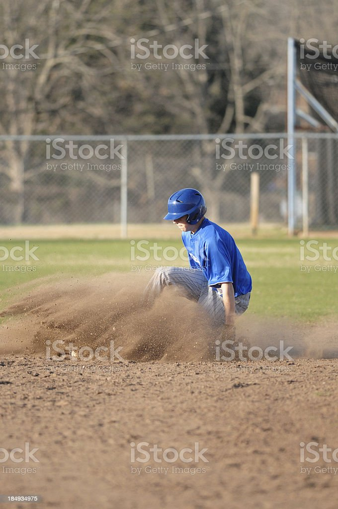 Base runner sliding into second in baseball game stock photo