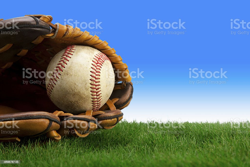 Baseball and glove on grass field stock photo