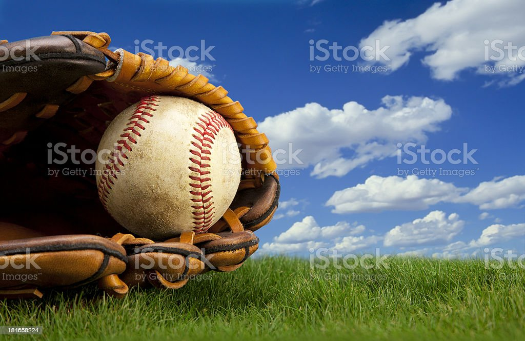 Baseball and glove on Grass with sky background stock photo